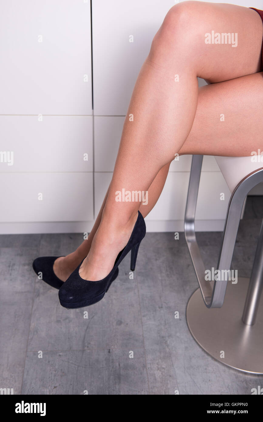 woman sitting with crossed legs on a chair in the office - Stock Image