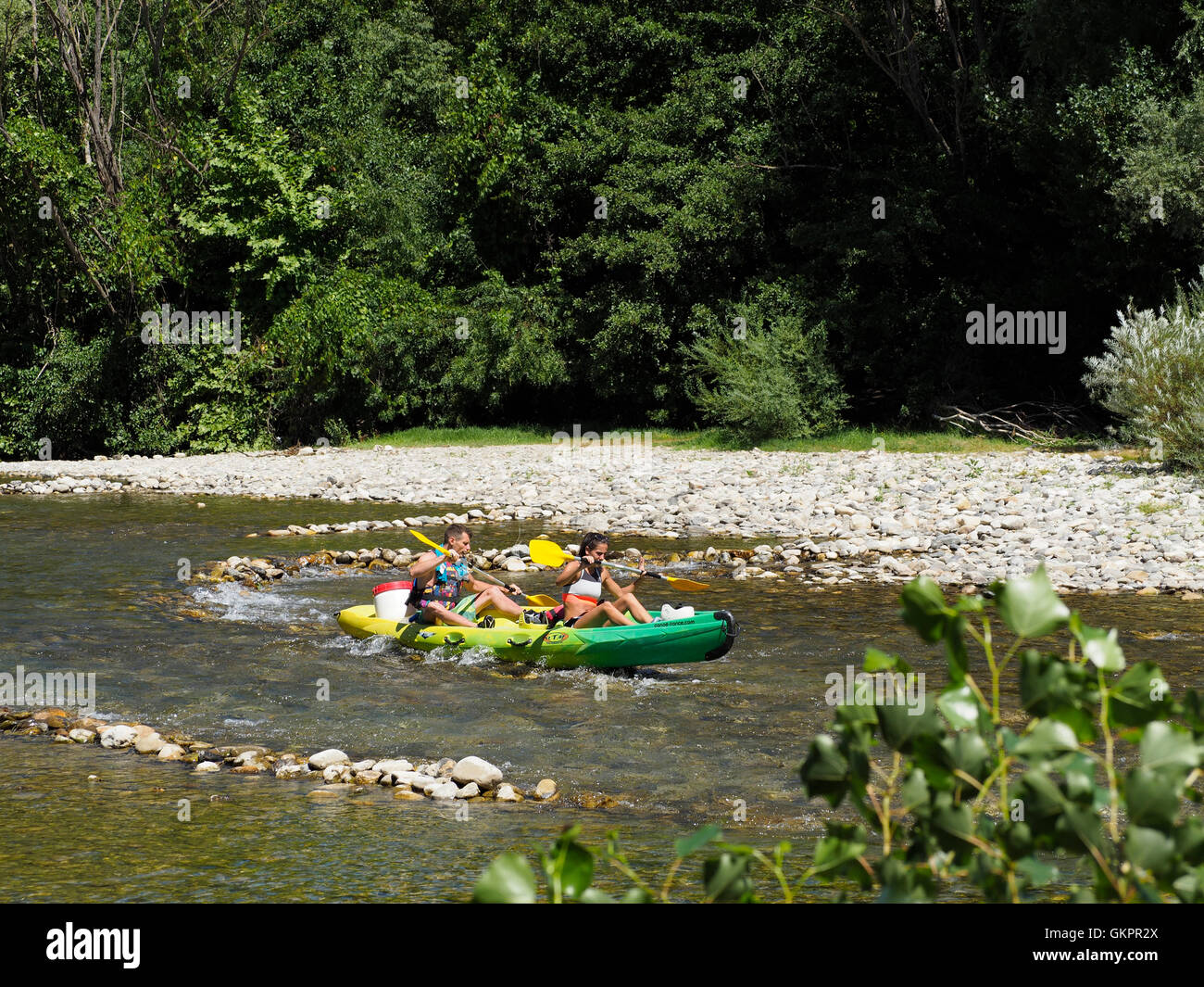 Couple making a canoe trip, a very popular activity in France, this is the Herault river in the Cevennes region. - Stock Image