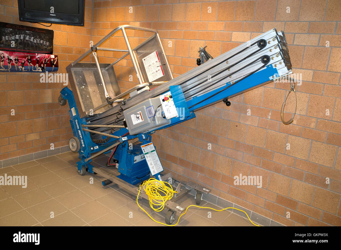Tilt-back Genie AWP-36S Aerial Work Platform in compact position at high school gymnasium. Lakeville Minnesota MN - Stock Image