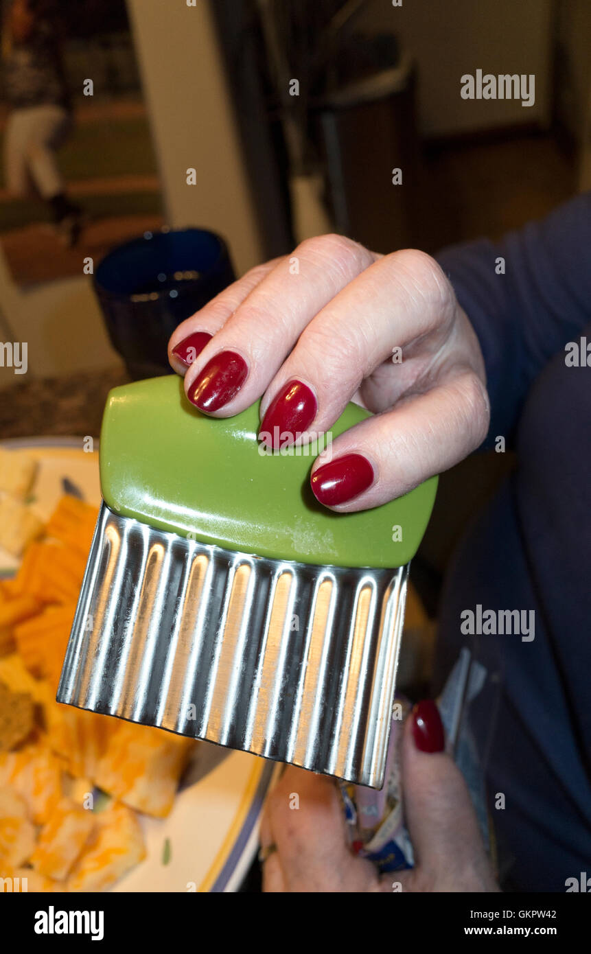 Woman with red painted nails holding up a serrated cheese shredder with a green handle. St Paul Minnesota MN USA - Stock Image