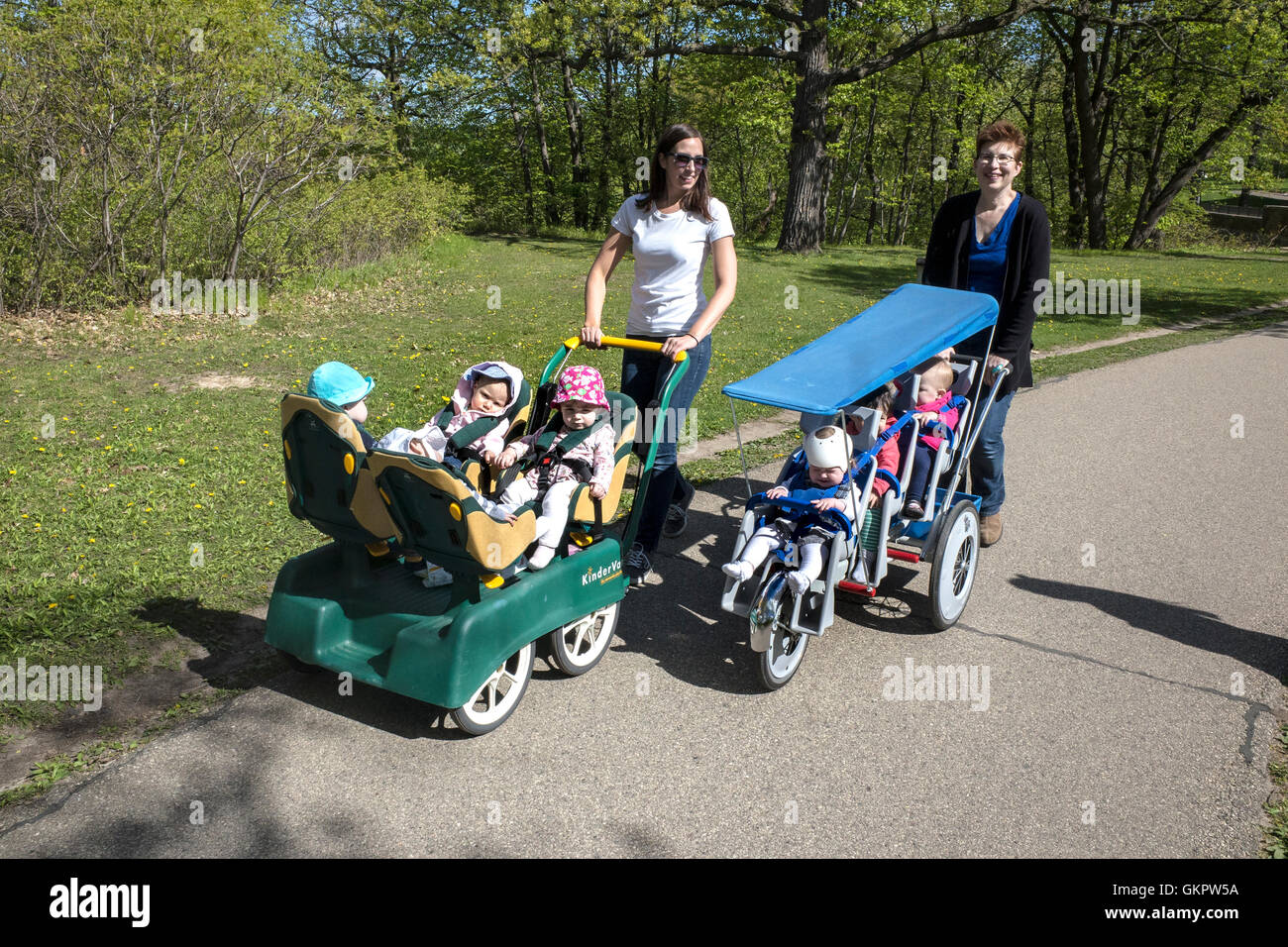 Daycare woman taking a walk with toddlers in multi fit strollers. North Mississippi River Boulevard. St Paul Minnesota - Stock Image
