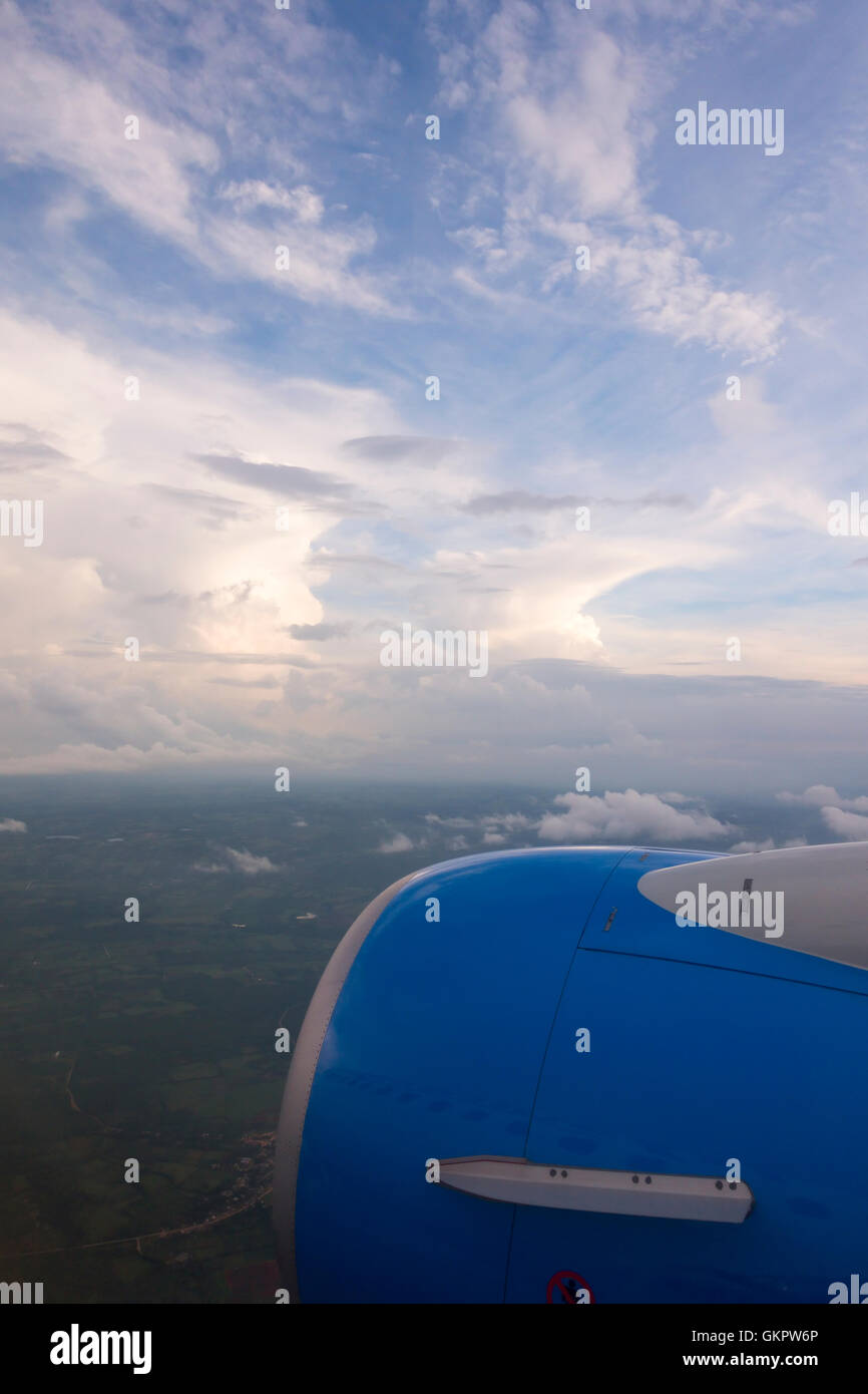 Altocumulus, Cumulonimbus and Cumulus clouds as seen from an airplane window with the engine in the photo. - Stock Image