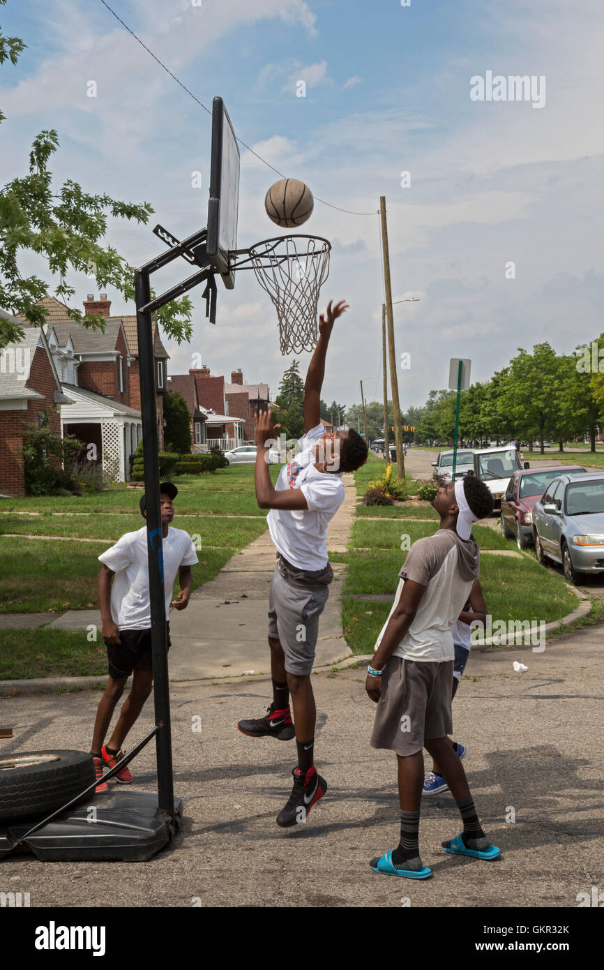 Detroit, Michigan - Teenage boys play basketball in the street during a summer street fair held by a neighborhood Stock Photo