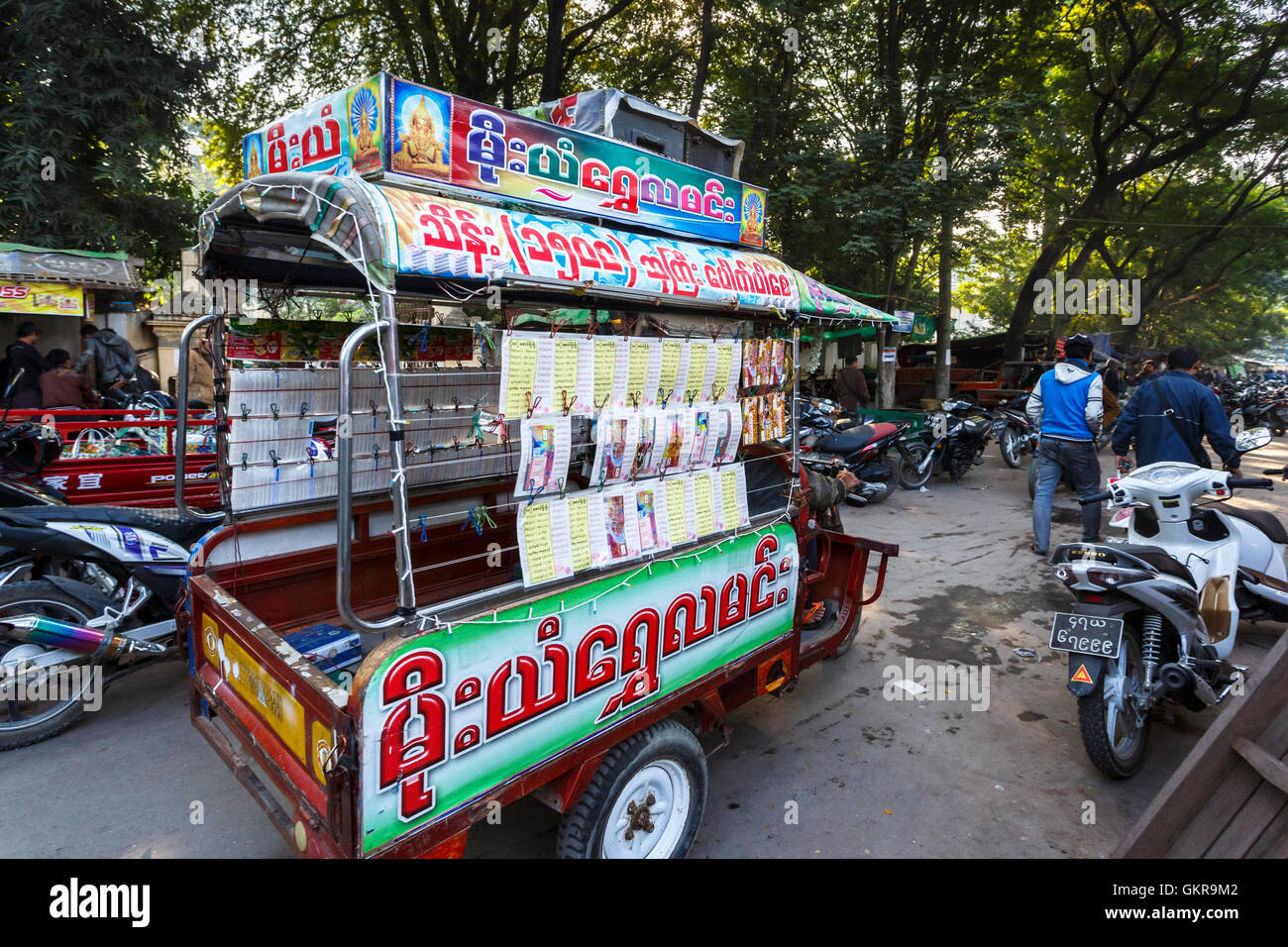 Three wheeled vehicle selling lottery tickets in the street at the