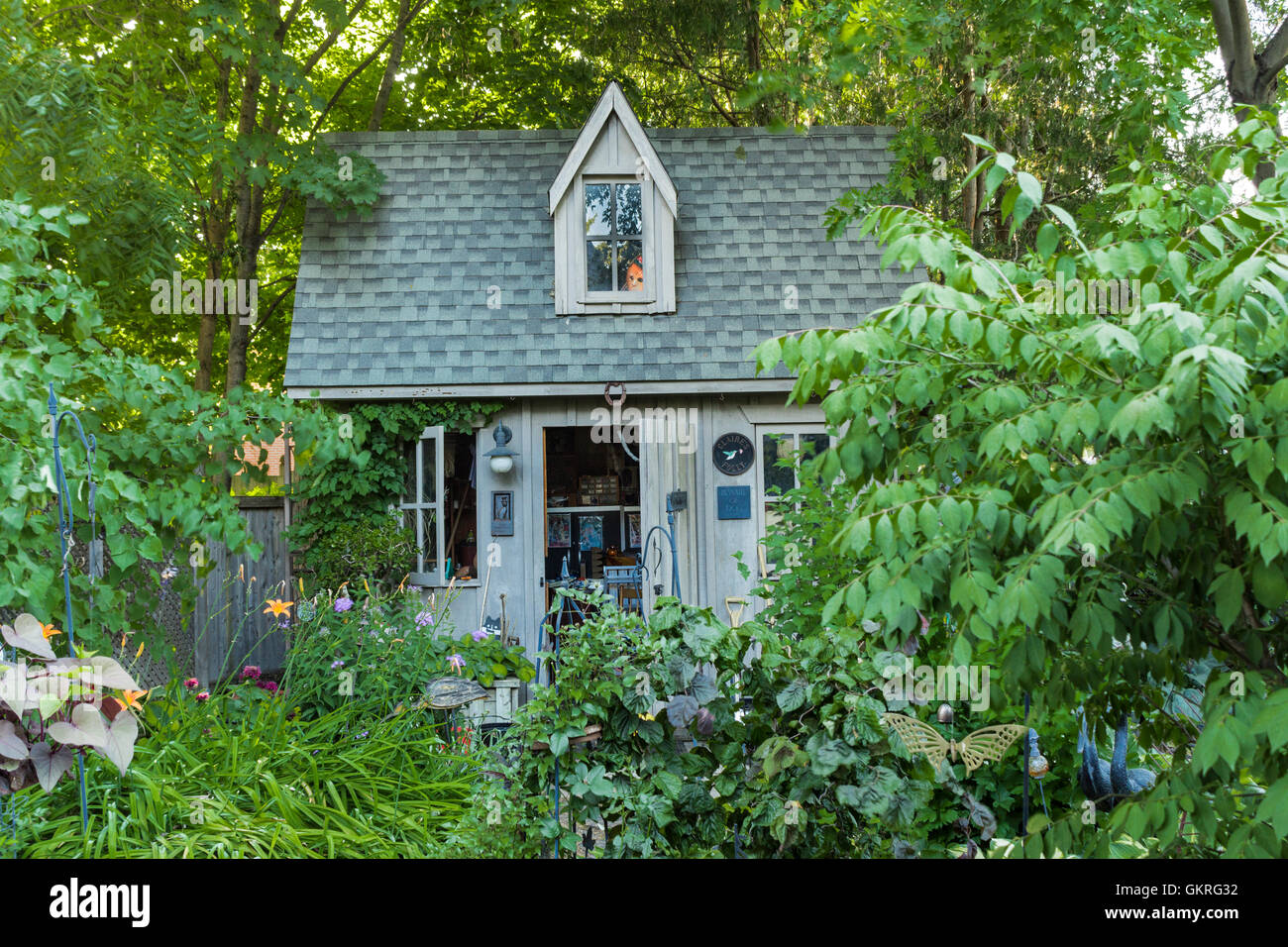 Large garden shed with dolls face in the window - Stock Image