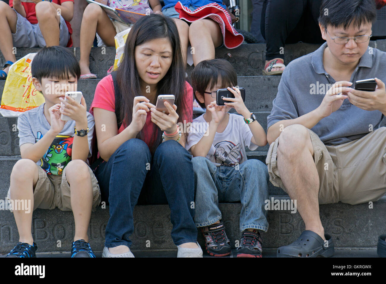 An Asian family sitting on the steps at the public library in Downtown Flushing, Queens, NYC, all using their cell - Stock Image