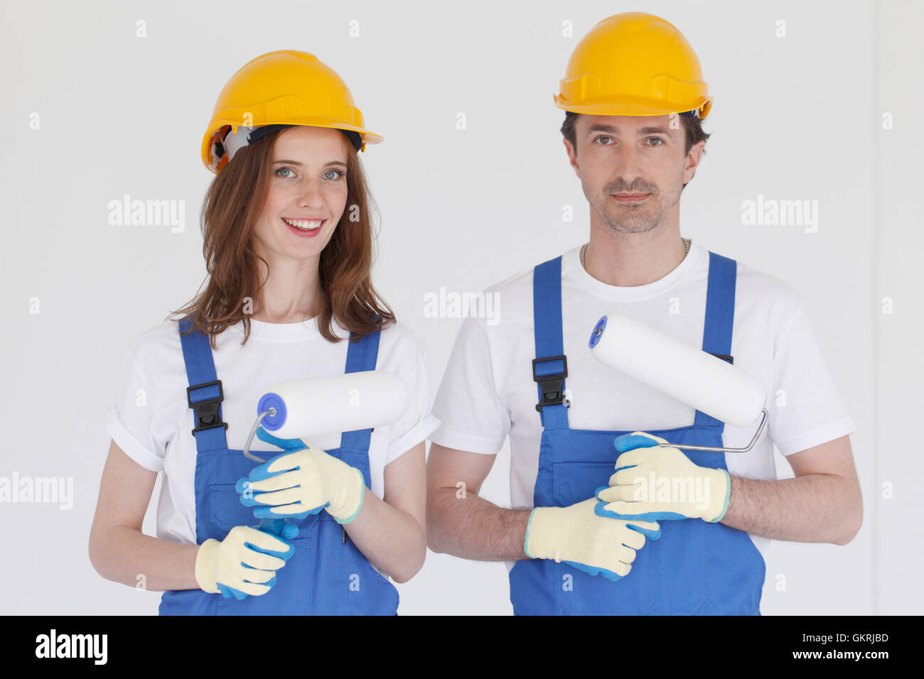 Happy couple in uniform holding paint rollers ready to work - Stock Image