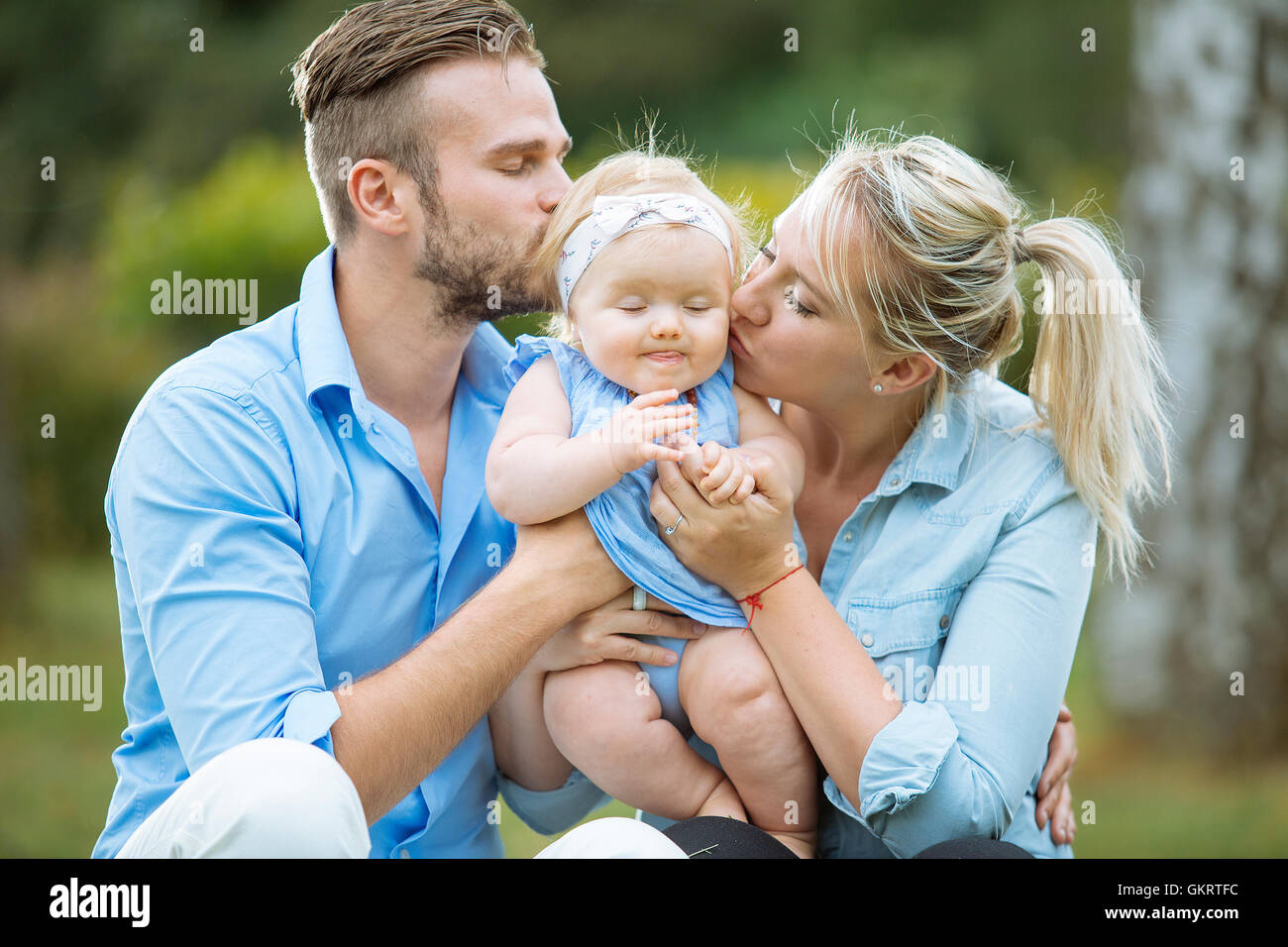 Portrait of parents kissing their baby girl - Stock Image