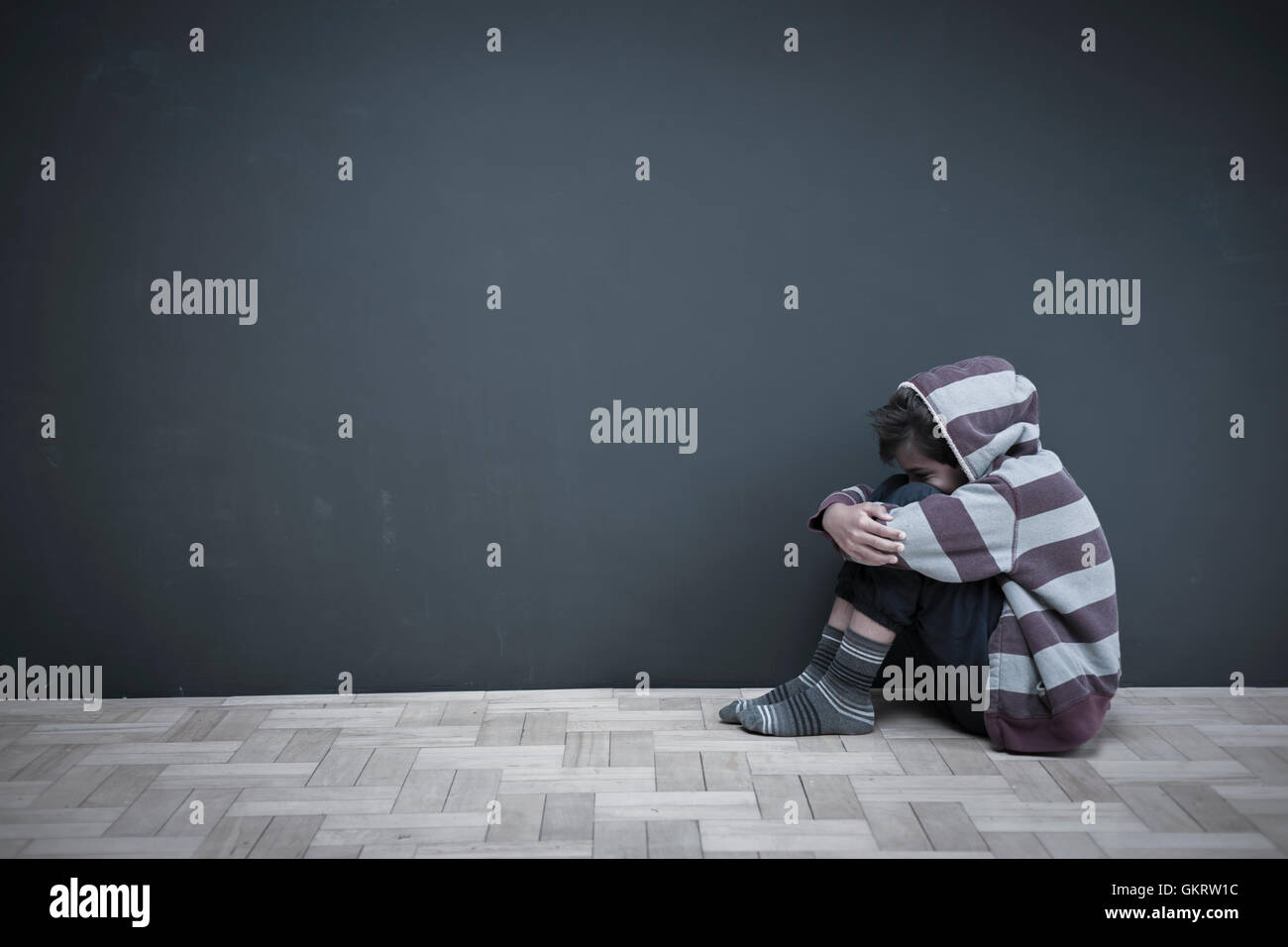 Boy sitting on floor wearing hooded top hugging knees - Stock Image
