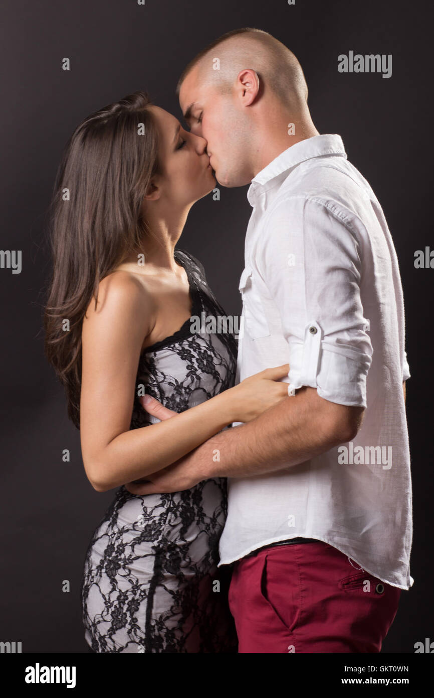 Young couple early 20s man woman kissing black background - Stock Image