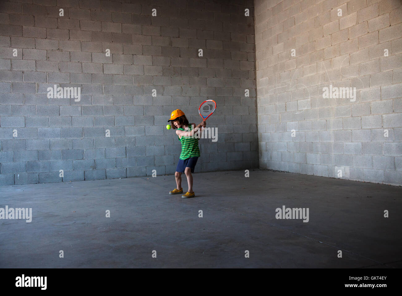 7 year old boy playing tennis in an empty half built shop. - Stock Image