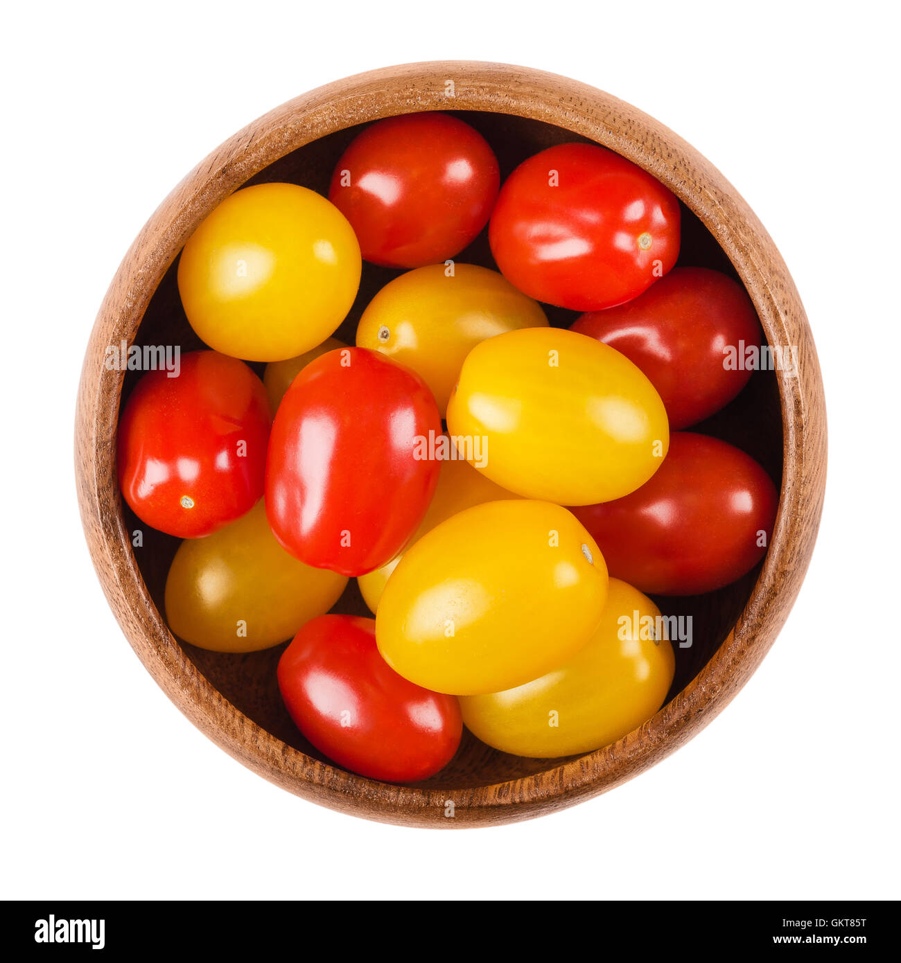 Cocktail tomatoes in a wooden bowl on white background. Yellow and red ripe fruits of Solanum lycopersicum, a berry - Stock Image