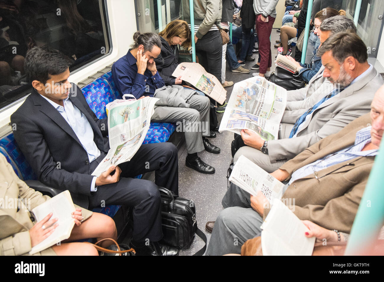 Locals reading newspapers and books inside London Underground tube train.About to arrive at Waterloo tube station,London.England - Stock Image