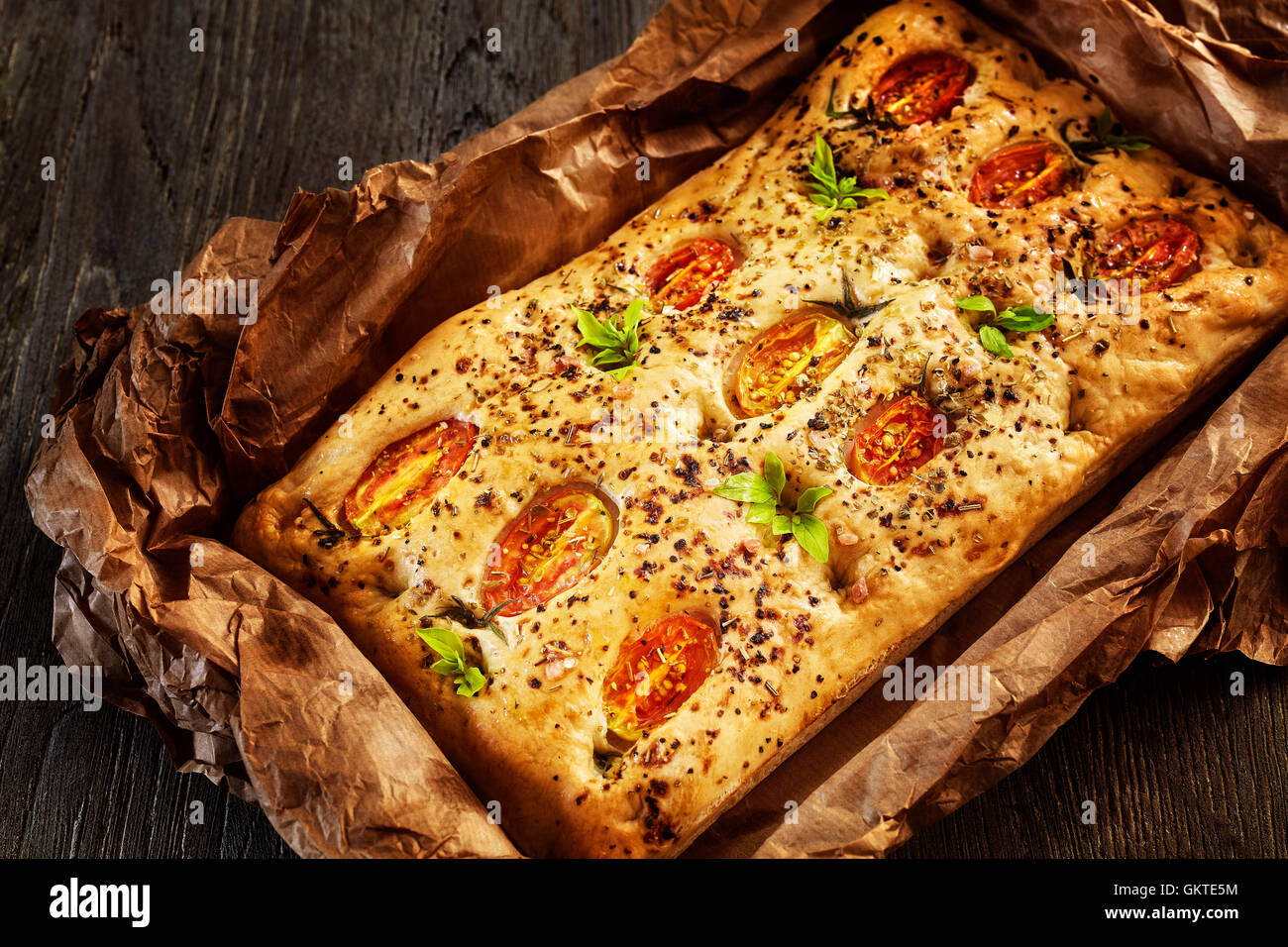 Freshly baked traditional Italian focaccia with tomatoes on an old wooden table. - Stock Image