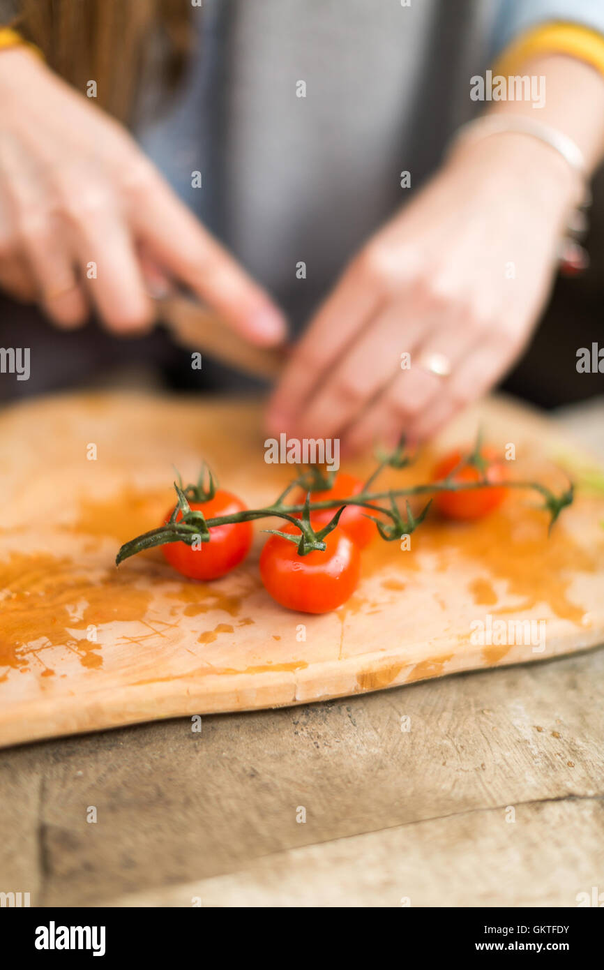 the girl cuts cherry tomatoes. - Stock Image