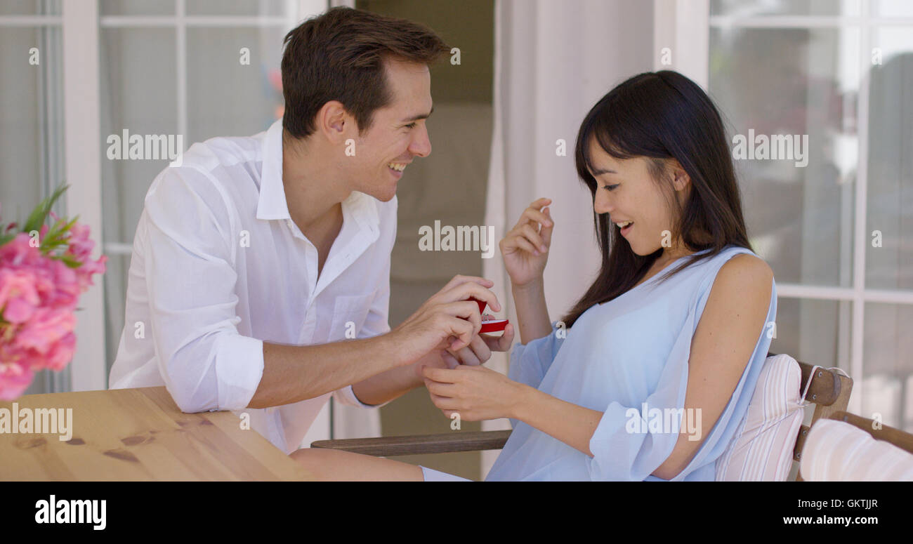 Man giving flattered woman a ring at table - Stock Image