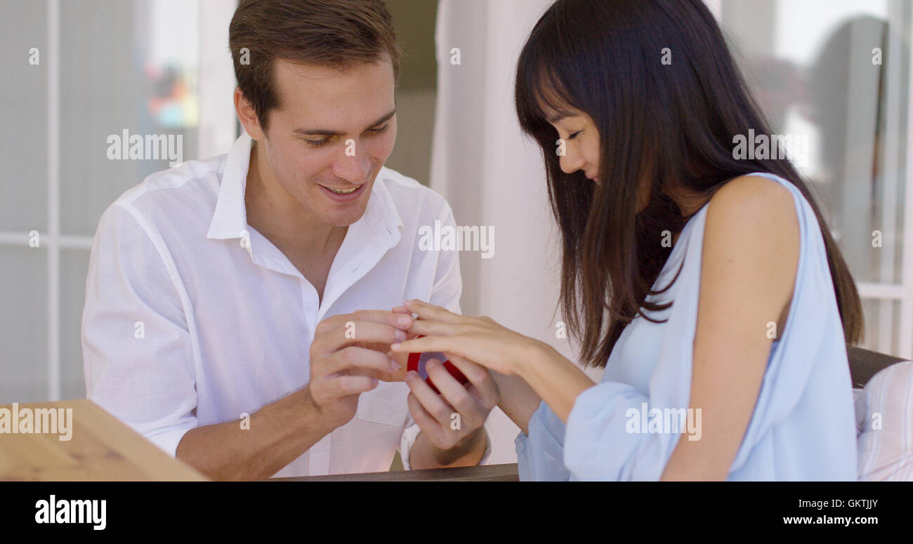Man fitting ring on finger of girlfriend - Stock Image