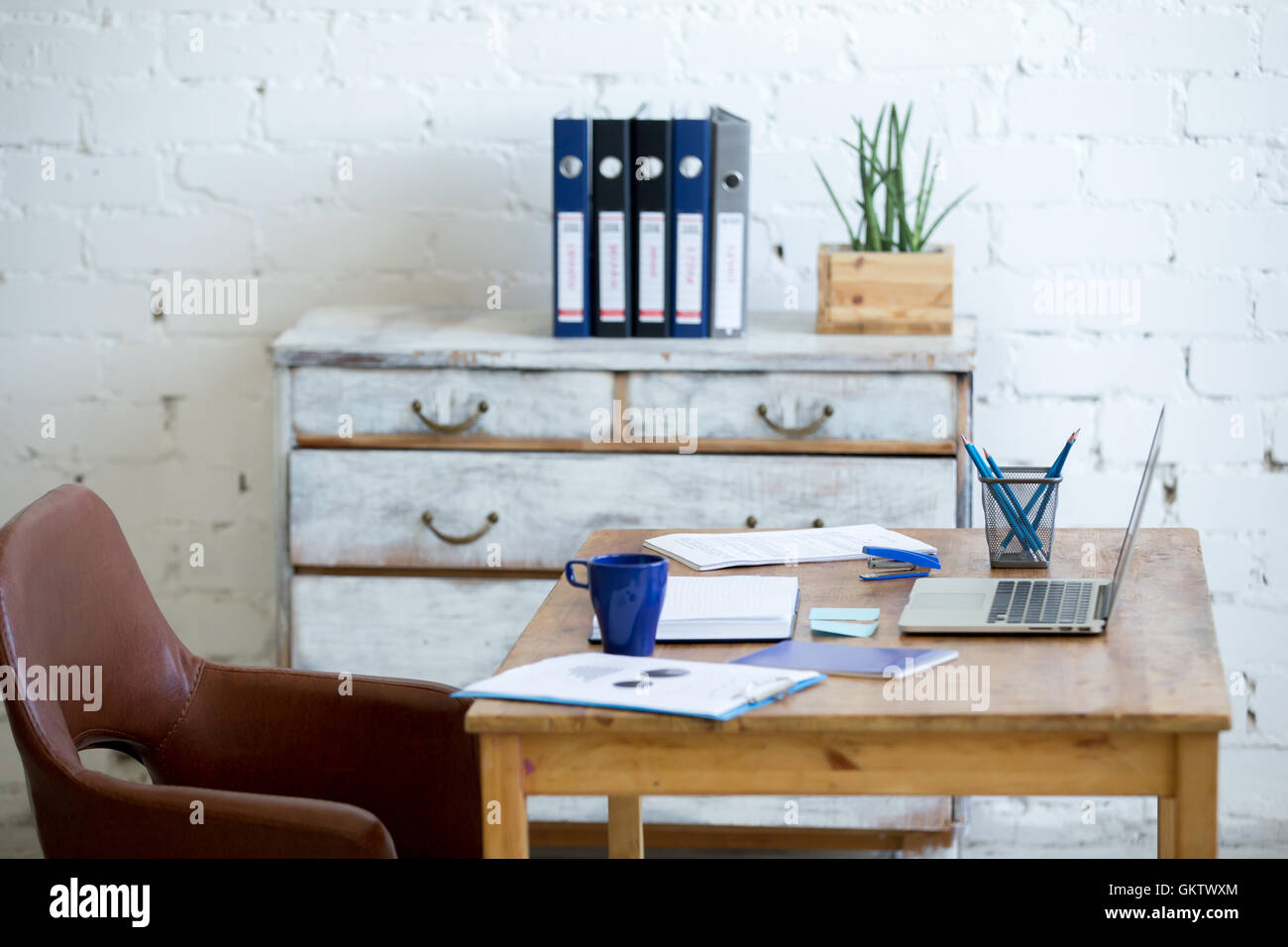 Home office interior in loft space with white brick walls. Cozy workplace with wooden table, office supplies, documents - Stock Image