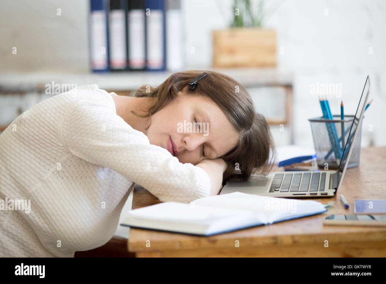 Portrait of young woman lying on the table in front of laptop, sleepy, tired, overworked or lazy to work. Attractive - Stock Image