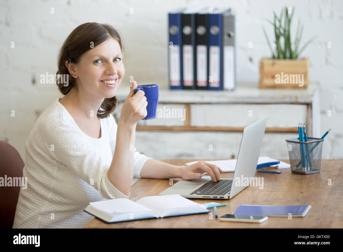 Portrait of young business woman drinking coffee and using laptop in home office interior. Happy casual office person - Stock Image