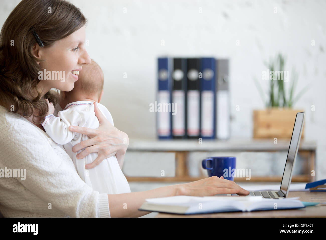 Side view portrait of happy casual young business mom holding her newborn cute babe while working on laptop in home - Stock Image