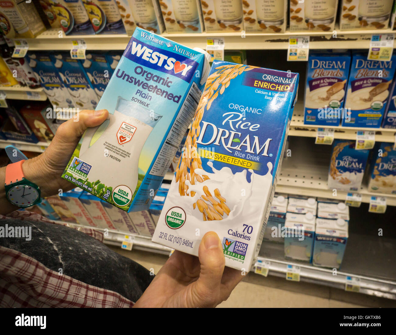 A shopper considers packages of WestSoy soy milk and Rice