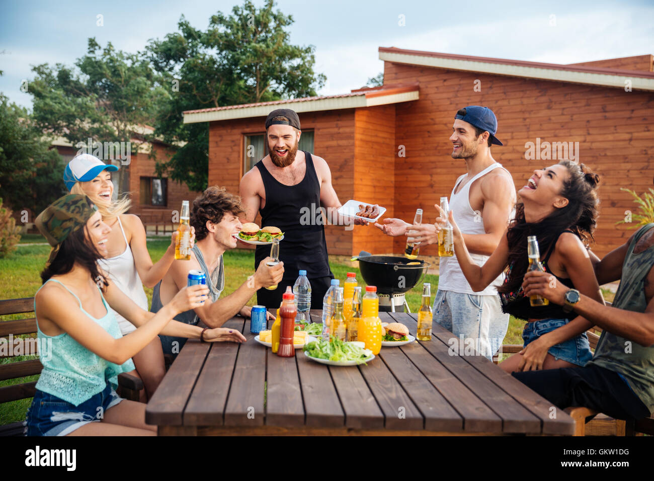 Group of happy young people laughing and having fun on barbeque party - Stock Image