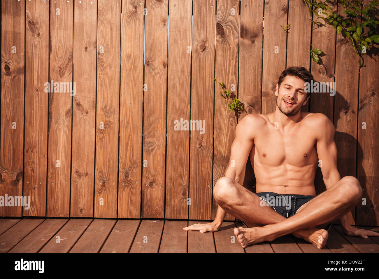 Young handsome smiling man in swimwear sitting with legs crossed over wooden background - Stock Image