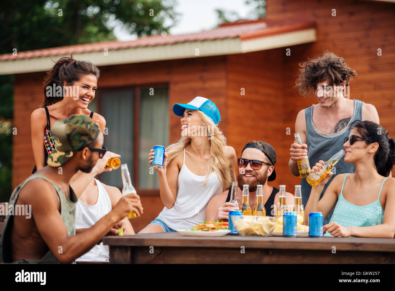 Group of cheerful young people drinking beer and soda and laughing outdoors - Stock Image