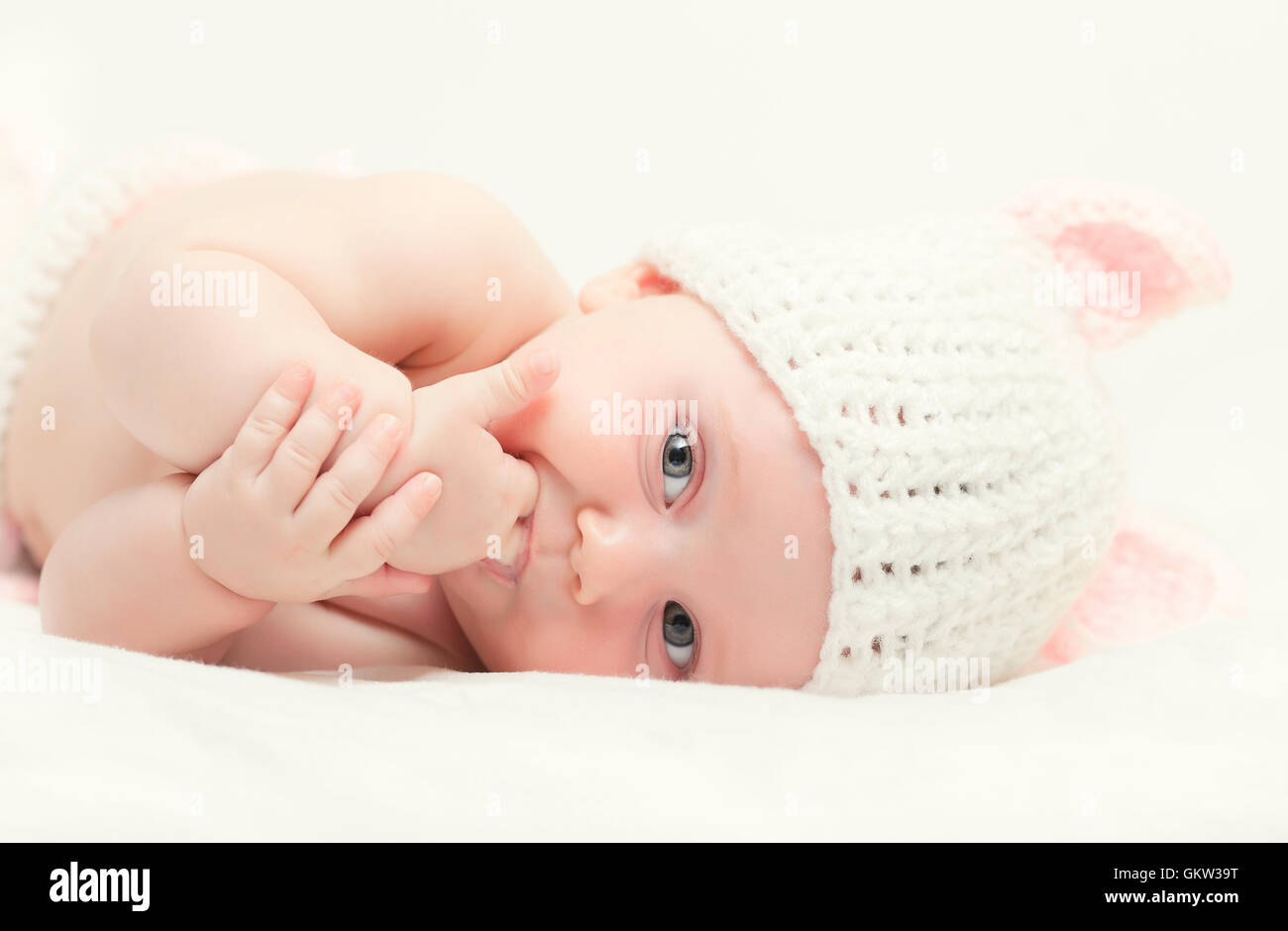 portrait of femail newborn with bunny woolen hat - Stock Image