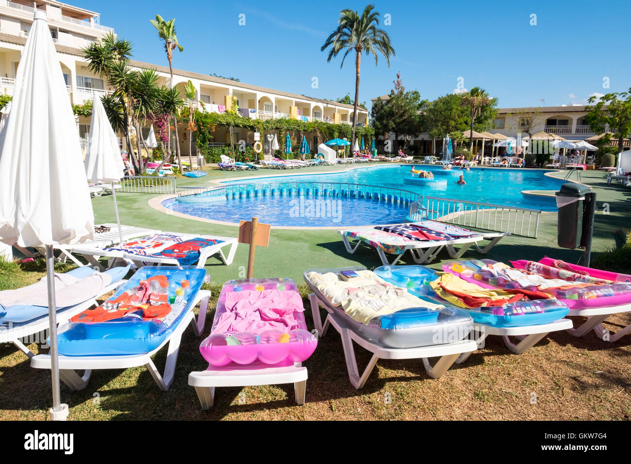 Towels left on sun beds around the pool in the morning by tourists reserving sun loungers for later in the day, - Stock Image