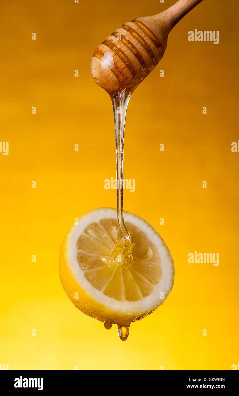Honey flowing on lemon Stock Photo