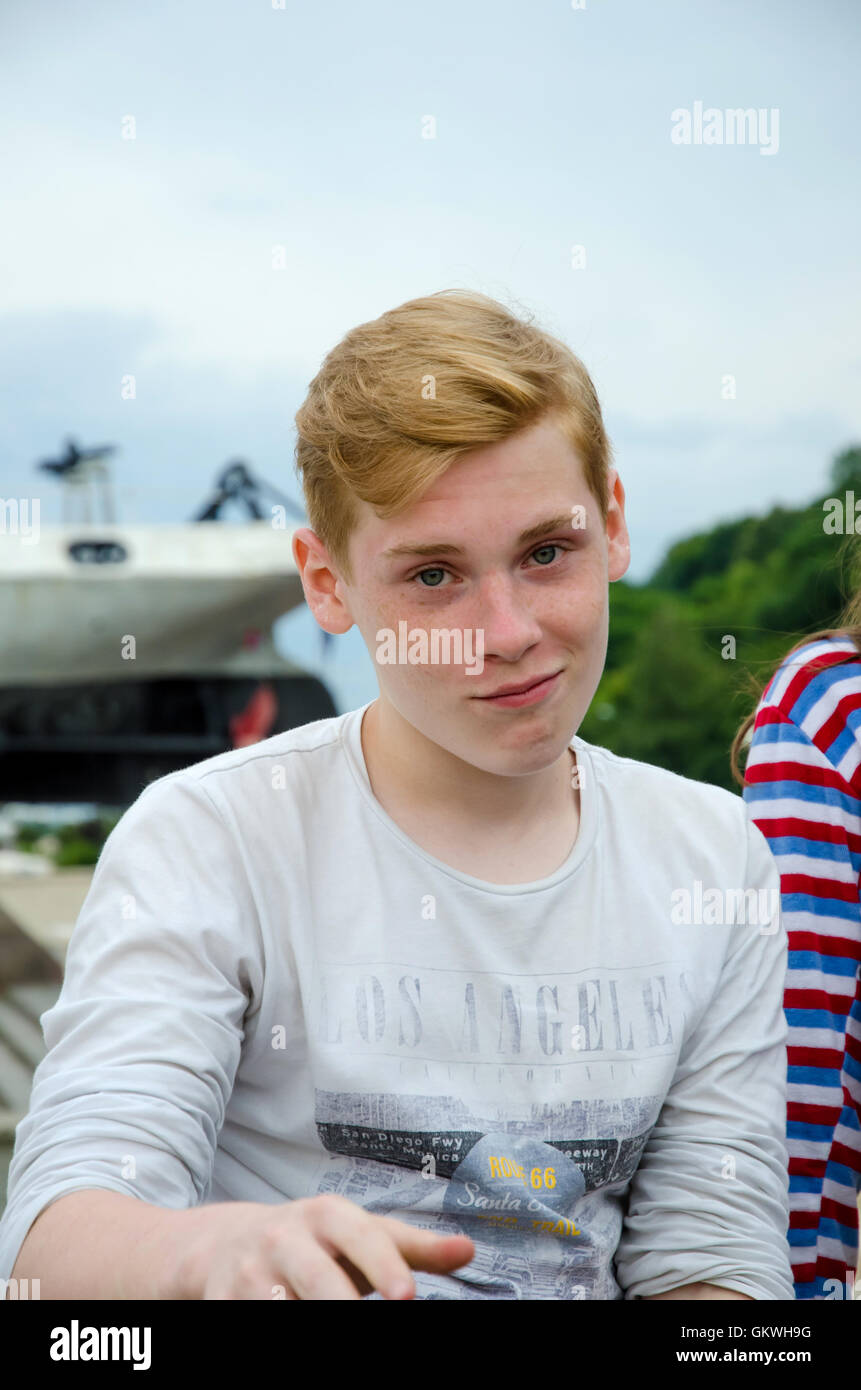 Teenager boy looking at camera with a grimace - Stock Image