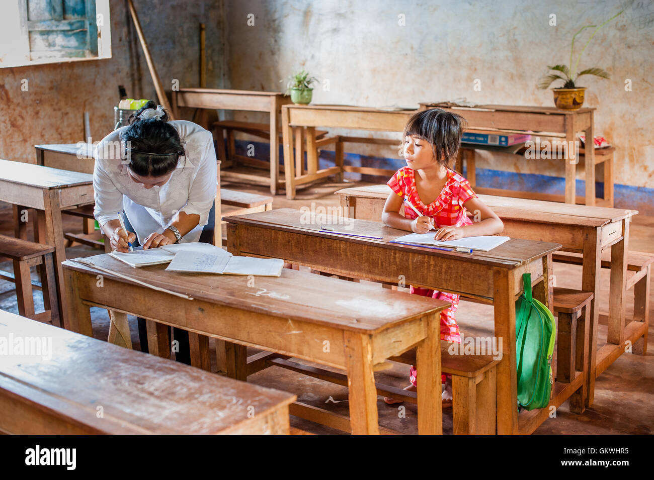 Girl with teacher at village school - Stock Image