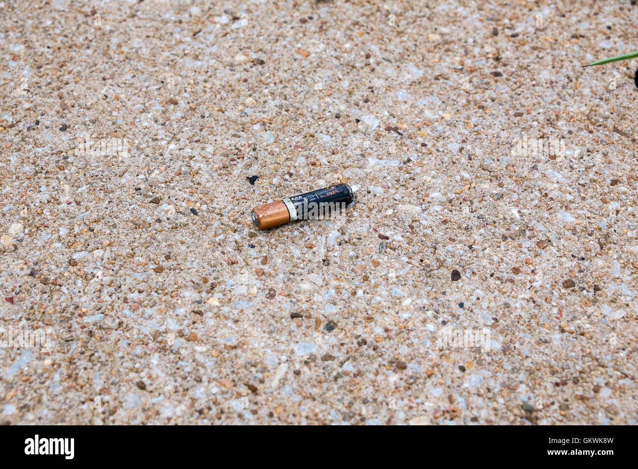 Crushed battery on pavement - Stock Image