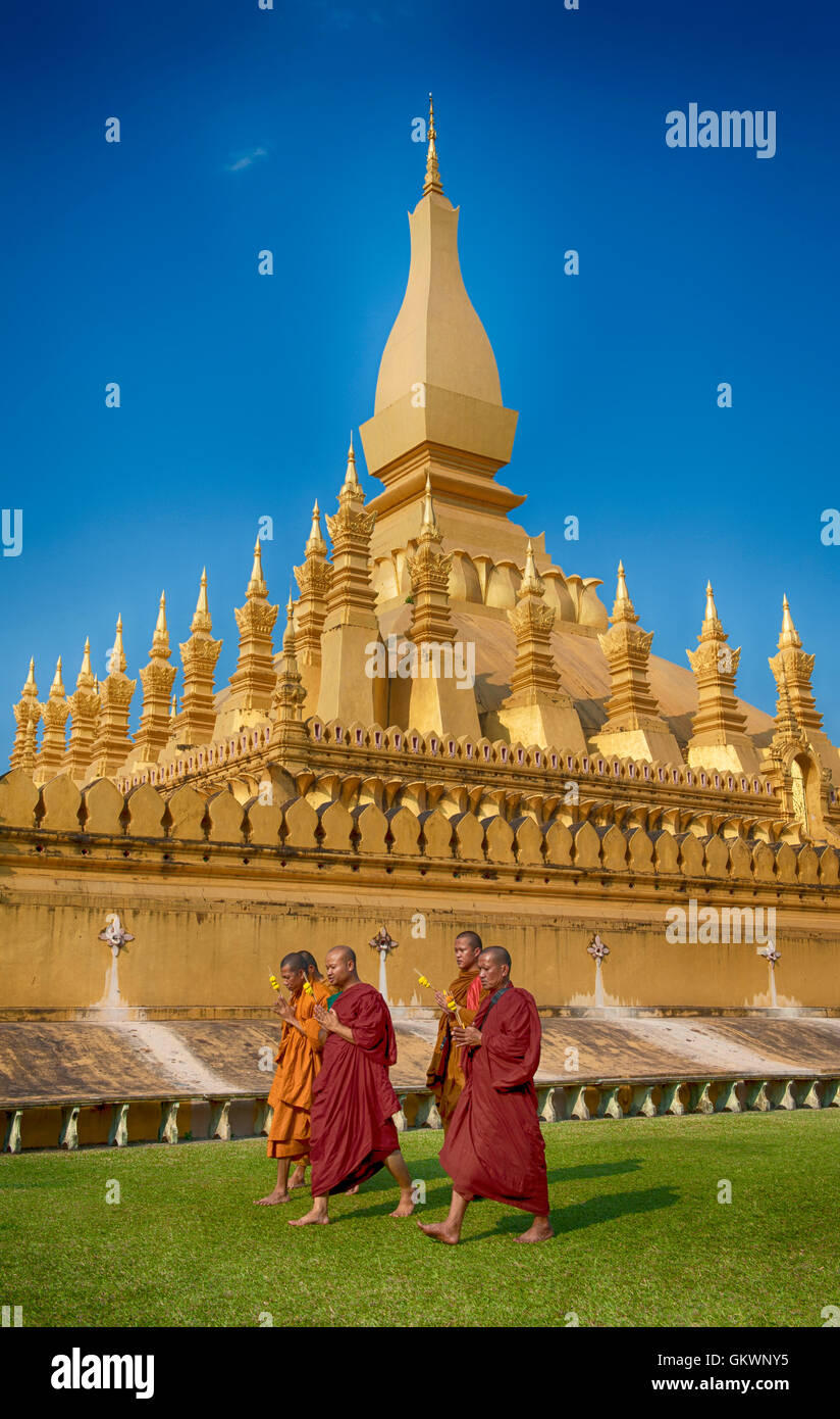 Vientiane, Laos - January 19, 2012:  Group of Buddhist monks walking around That Luang Stupa, landmark of Vientiane, - Stock Image