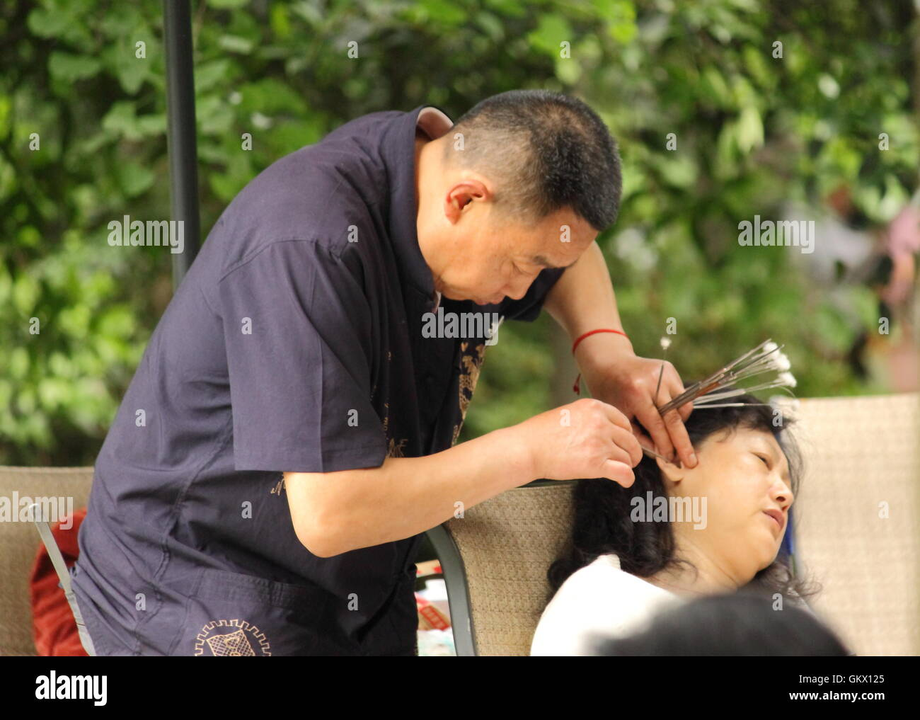 A man cleans ear wax using traditional tolls in People's park in Chengdu China. - Stock Image
