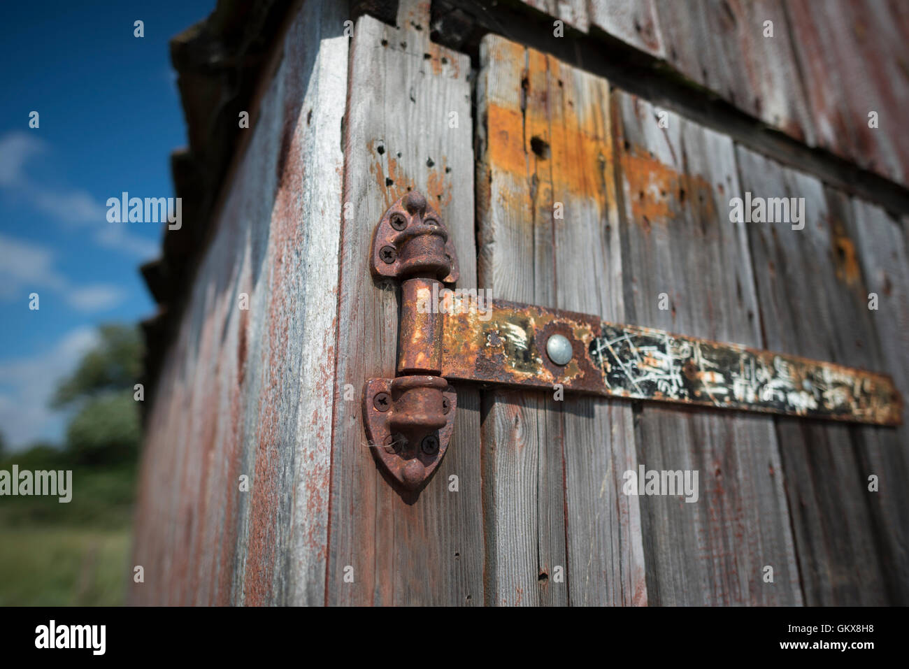Closeup of an old rusty hinge on a boathouse - Stock Image