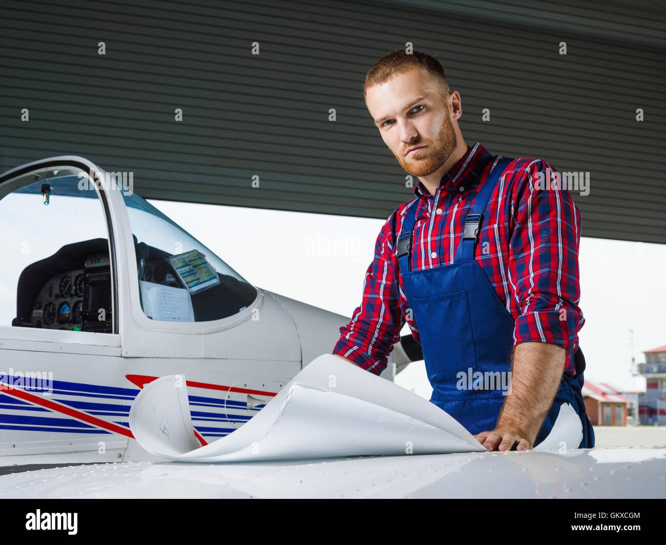 Serious aircraft mechanic looking at camera - Stock Image