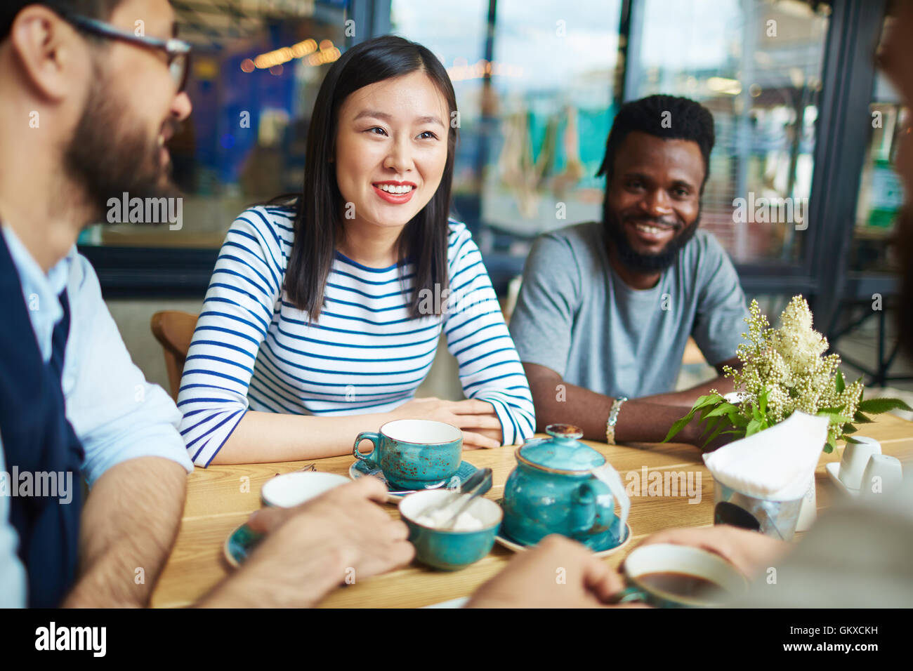 Happy intercultural friends having nice time by cup of tea in cafe - Stock Image