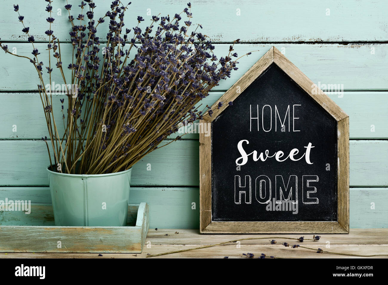 closeup of a house-shaped chalkboard with the text home sweet home written in it and a bunch of lavender flowers - Stock Image
