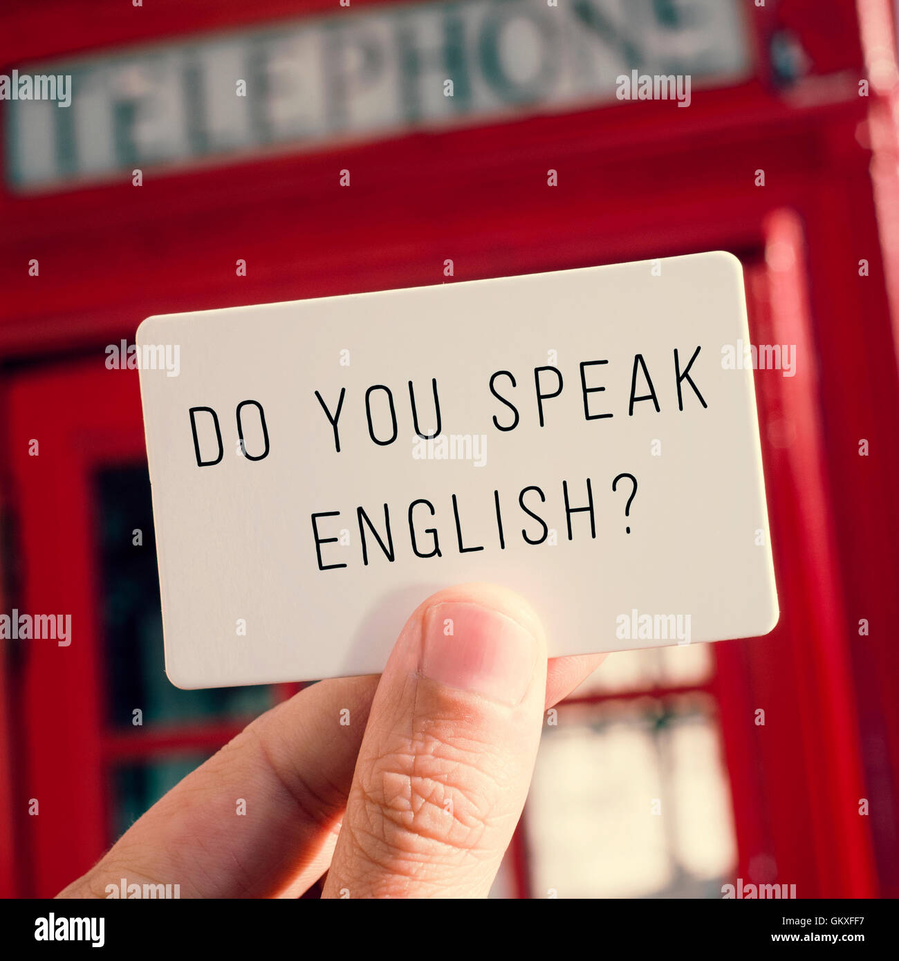 a man holding a signboard with the text do you speak english? with a typical british red telephone booth in the - Stock Image