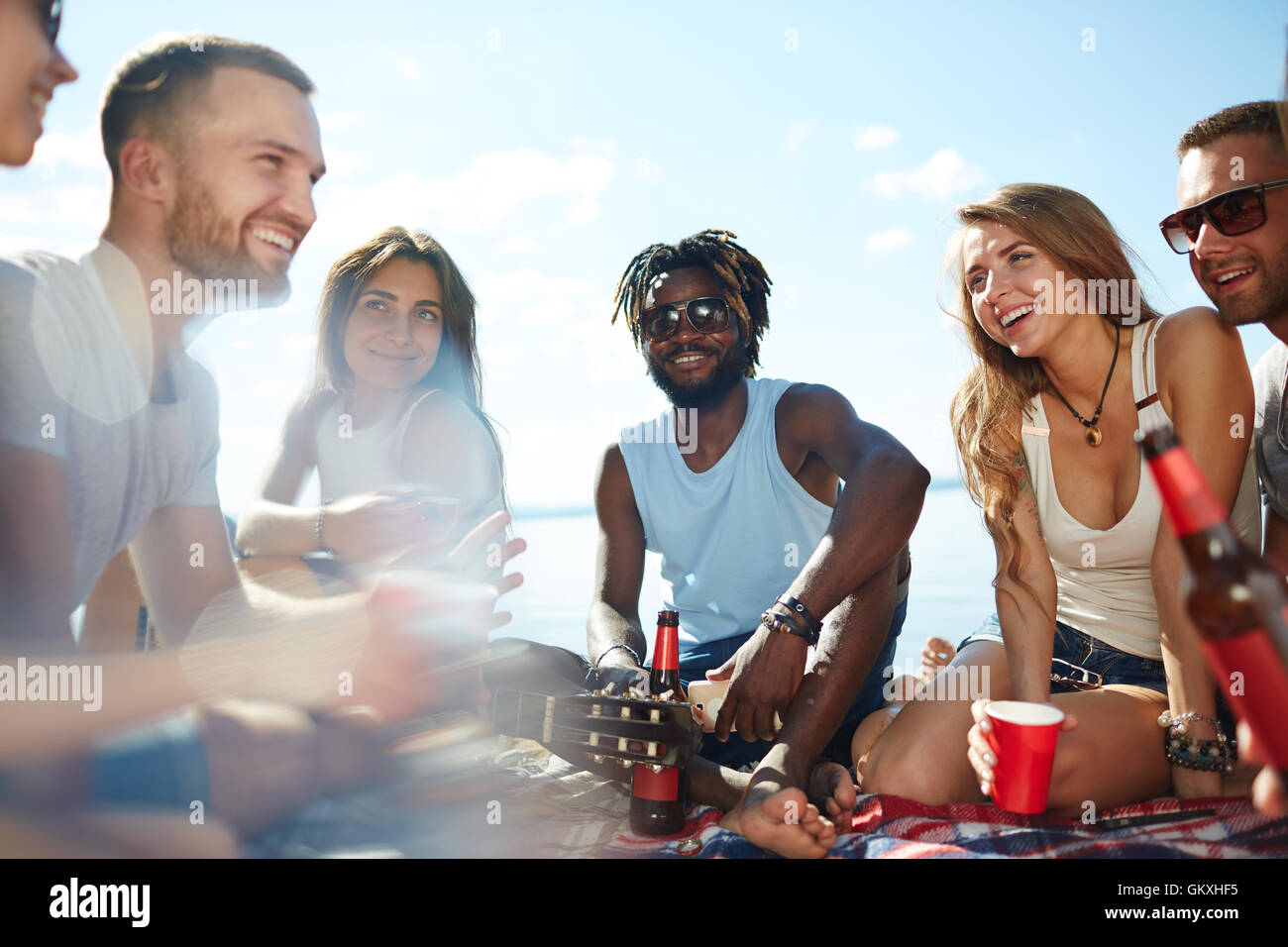 Group of joyful friends having nice time on the beach - Stock Image