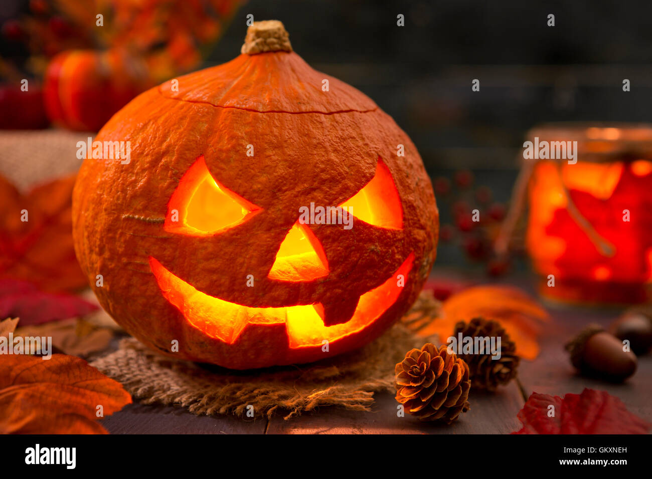 Burning Jack O'Lantern on a rustic table with autumn decorations, darkly lit. Stock Photo