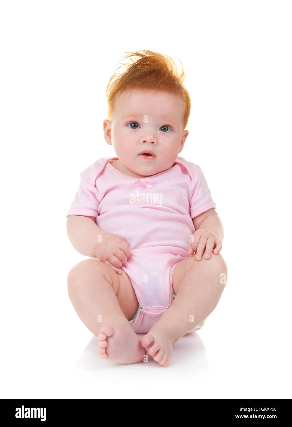 Smiling baby in pink jumpsuit sitting on the floor isolated on white background - Stock Image