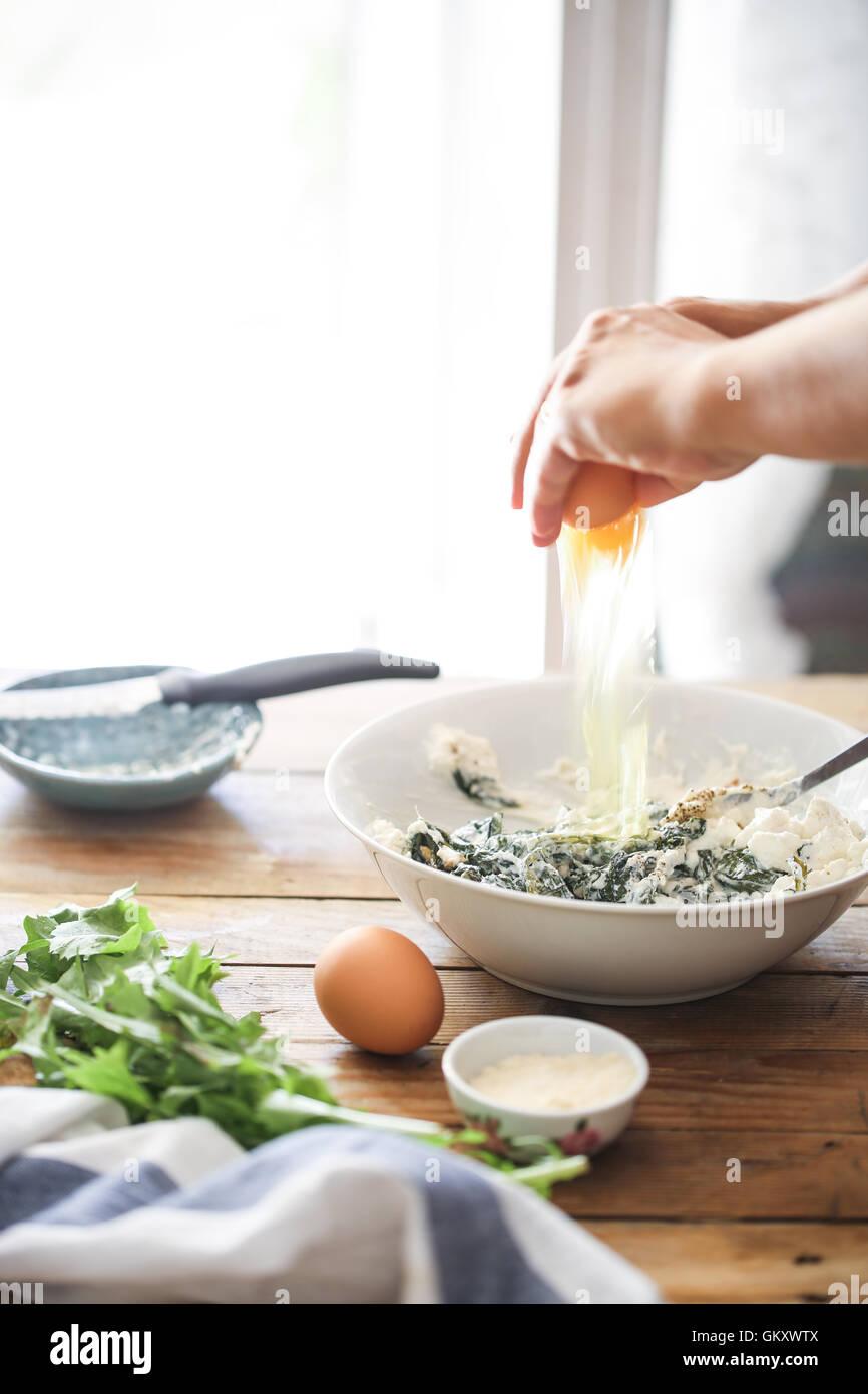 A woman broke an egg into a bowl to prepare homemade herbs tart - Stock Image
