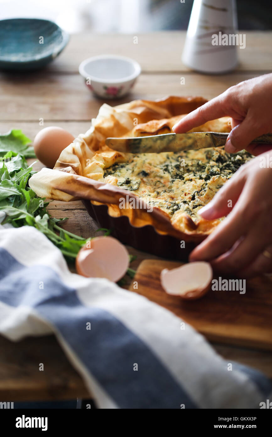 A woman cut a Provencal tart with herbs - Stock Image