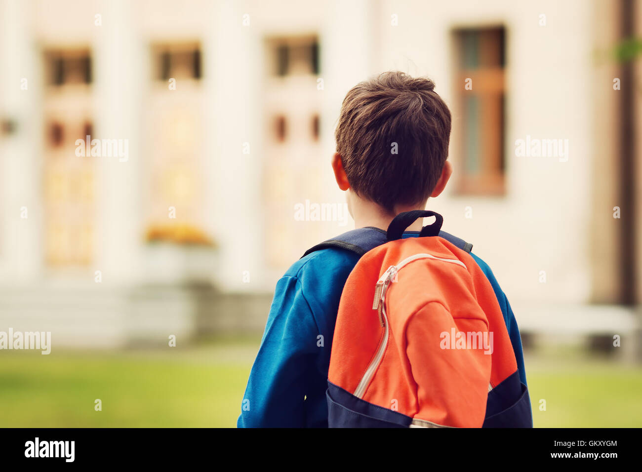 Boy with rucksack infront of a school building - Stock Image
