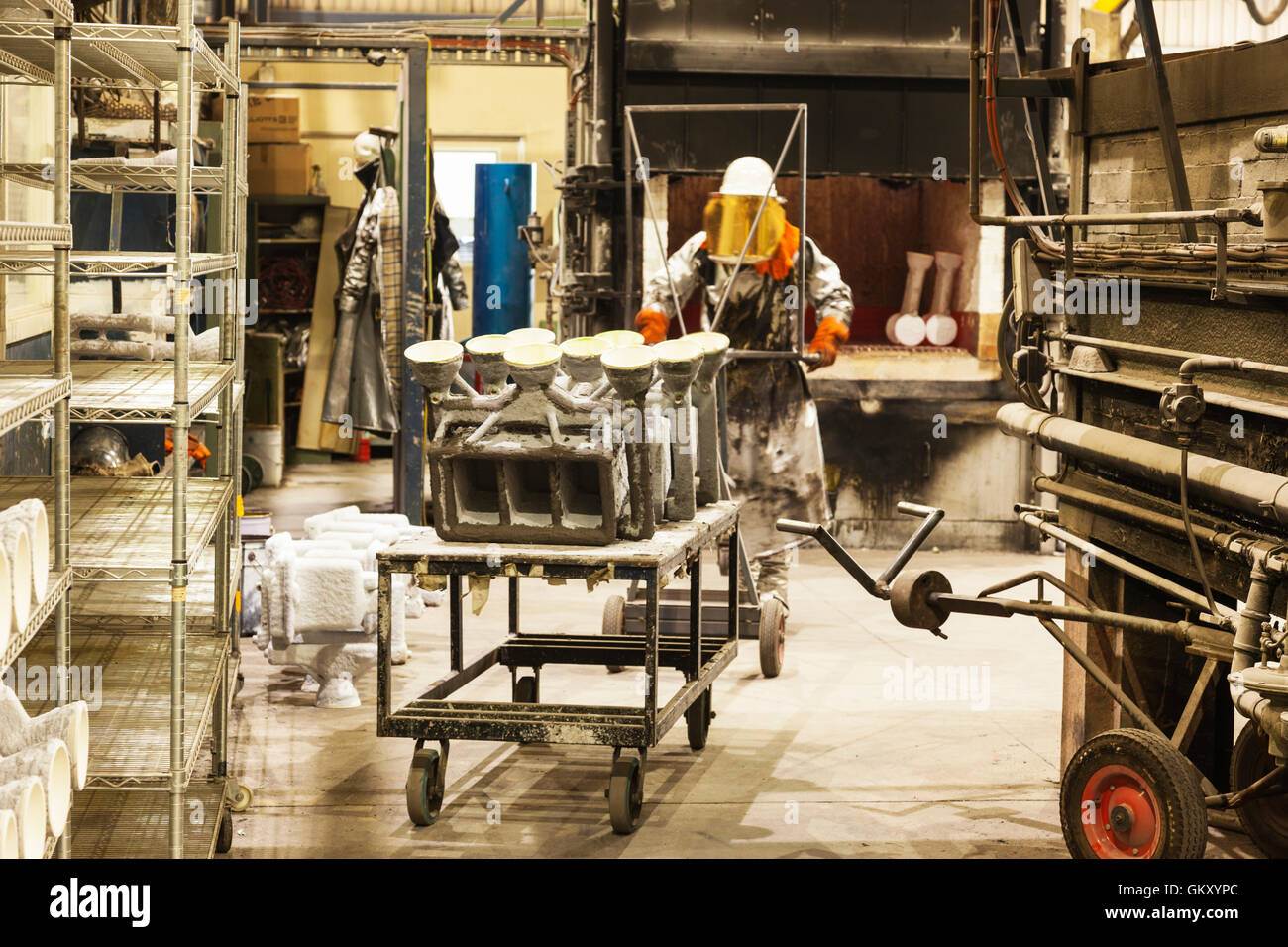 workmen in safety wear cutting, grinding metal parts for further processing manufacturing component parts for assembly - Stock Image