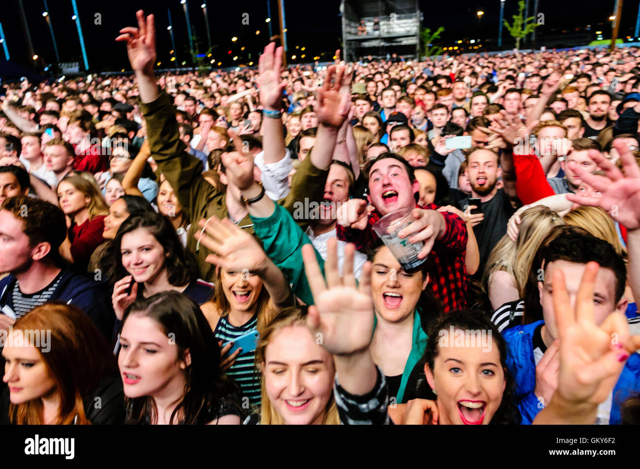 A crowd of people, late teenagers to mid to late twenties, are excited at a music festival. Some have plastic glasses - Stock Image